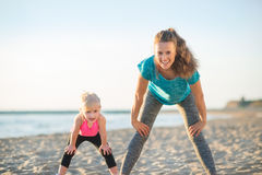 Healthy mother and baby girl workout on beach Stock Image