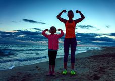Healthy mother and child on seacoast on sunset showing biceps. Look Good and feel great. Silhouette. healthy mother and child in sport style clothes on the stock photo