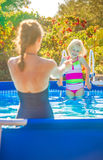 Healthy mother and child in swimsuit in swimming pool playing Stock Image