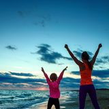 Healthy mother and daughter on seacoast on sunset rejoicing Stock Image