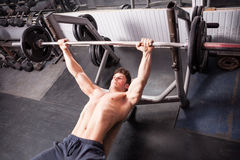 Healthy muscular guy doing exercises in the gym Royalty Free Stock Image