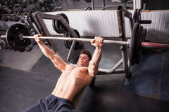 Healthy muscular guy doing exercises in the gym Stock Photography