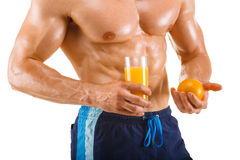 Healthy muscular man holding a glass with juice and orange, shaped abdominal, isolated Stock Photos
