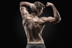 Healthy muscular young man showing back and biceps muscles Royalty Free Stock Images