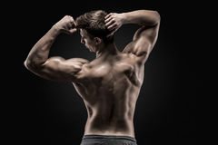 Healthy muscular young man showing back and biceps muscles Stock Photo