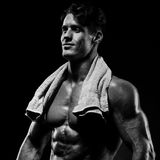 Healthy muscular young man after a workout on dark background. Stock Photo