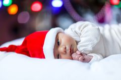 Healthy newborn baby in Santa hat near Christmas tree with colorful garland lights on background. Closeup of cute child royalty free stock photo