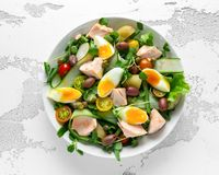Healthy Nicoise salad with salmon, colourful sweet cherry tomatoes, olives, green beans, cucumber ribbons, soft boiled Stock Image