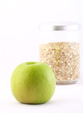 Healthy nourishment: oat flakes and green apple. Isolated on white Royalty Free Stock Images