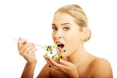 Healthy nude woman eating cuckooflower Stock Images