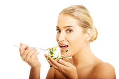 Healthy nude woman eating cuckooflower Royalty Free Stock Image
