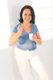 Healthy nutrition. Elder woman eating yoghurt. She's smiling and looking at camera Royalty Free Stock Image