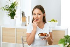 Healthy Nutrition. Beautiful Young Woman Eating Nuts. Portrait Of Happy Smiling Female Eating Almonds For Breakfast In Kitchen. Healthy Lifestyle And Diet stock photos