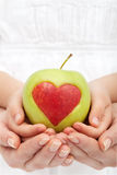 Healthy nutrition concept. Hands holding apple with heart cutout royalty free stock images