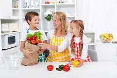 Healthy nutrition concept. With people in the kitchen unpacking the vegetables from grocery bag royalty free stock photography