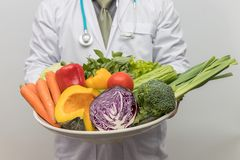 Healthy and nutrition concept. Doctor holding bowl of fresh fruits and vegetables.  stock image