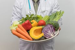 Healthy and nutrition concept. Doctor holding bowl of fresh fruits and vegetables.  stock photo
