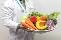 Healthy and nutrition concept. Doctor holding bowl of fresh fruits and vegetables.  royalty free stock photo