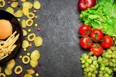 Healthy nutrition concept. Fruits and vegetables vs unhealthy fa Stock Photography