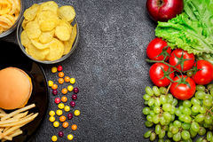 Healthy nutrition concept. Fruits and vegetables vs unhealthy fa. St food and sweets. Contrasting food stock images