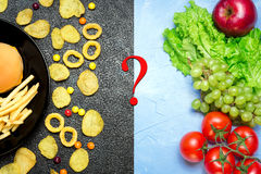 Healthy nutrition concept. Fruits and vegetables vs unhealthy fa. Healthy nutrition concept. Fruits and vegetables on light table vs unhealthy fast food and royalty free stock images