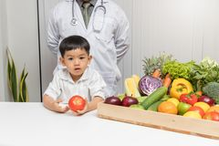 Healthy and nutrition concept. Kid learning about nutrition with doctor to choose eating fresh fruits and vegetables.Young asian b. Oy holding tomato royalty free stock images