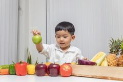 Healthy and nutrition concept. Kid learning about nutrition to choose how to eat fresh fruits and vegetables.  royalty free stock photo