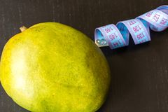 Healthy nutrition concept, mango and measuring tape on black background royalty free stock photo