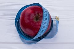 Healthy nutrition concept. Tape measure wrapped around red apple. Slimming diet and health care royalty free stock images