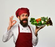 Healthy nutrition and cuisine concept. Cook with smile. In burgundy uniform holds salad ingredients. Man with beard isolated on white background. Chef holds stock images