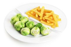 Healthy nutrition diet concept. French fries and brussels sprouts. Healthy and unhealthy junk food. Nutrition diet concept. French fries and brussels sprouts royalty free stock photos
