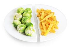 Healthy nutrition diet concept. French fries and brussels sprouts. Healthy and unhealthy junk food. Nutrition diet concept. French fries and brussels sprouts stock image