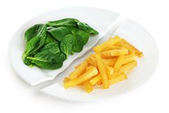 Healthy nutrition diet concept. French fries and spinach. Healthy and unhealthy junk food. Nutrition diet concept. French fries and spinach. Healthy and stock photo