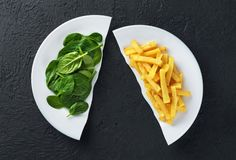 Healthy nutrition diet concept. French fries and spinach. Healthy and unhealthy junk food. Nutrition diet concept. French fries and spinach. Healthy and stock photography