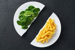 Healthy nutrition diet concept. French fries and spinach. Healthy and unhealthy junk food. Nutrition diet concept. French fries and spinach. Healthy and royalty free stock image