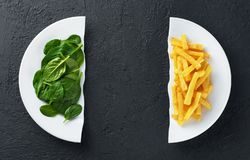 Healthy nutrition diet concept. French fries and spinach. Healthy and unhealthy junk food. Nutrition diet concept. French fries and spinach. Healthy and royalty free stock photography