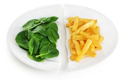 Healthy nutrition diet concept. French fries and spinach. Healthy and unhealthy junk food. Nutrition diet concept. French fries and spinach. Healthy and royalty free stock images