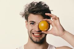 Healthy nutrition and diet concept. Man with orange covering one eye in his hand. Athlete with messy hair holds fresh fruit. Guy with happy face isolated on royalty free stock photos