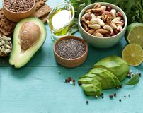 Healthy and nutrition food. Avocado, chia and flax seeds, olive oil and vegetables Stock Images