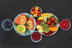 Healthy Nutrition for Good Health. Concept with super foods of fresh salmon fish, fruit, vegetables, herbs and olive oil very high in antioxidants, anthocyanins royalty free stock photos