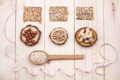 Healthy nutrition. Overhead view of different types of nuts and oat in wooden spoon wrapped in measure tape in diet , weight loss and healthy nutrition concept Stock Images