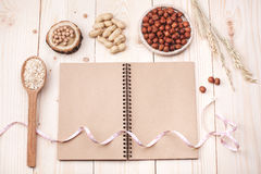 Healthy nutrition. Overhead view of a notebook, nuts and oat, wrapped in measure tape in diet , weight loss and healthy nutrition concept  lying   On wooden Stock Image