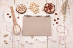 Healthy nutrition. Overhead view of a notebook, nuts and oat, wrapped in measure tape in diet , weight loss and healthy nutrition concept  lying   On wooden Stock Photo
