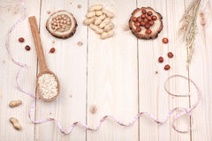 Healthy nutrition. Overhead view of a notebook, nuts and oat, wrapped in measure tape in diet , weight loss and healthy nutrition concept  lying   On wooden Stock Photos