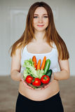 Healthy nutrition and pregnancy. Close-up pregnant woman's belly and vegetable salad. A beautiful pregnancy woman eating