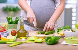 Healthy nutrition of pregnant woman. Pregnant woman cutting cucumber for fresh green salad, female prepares tasty organic dinner at home, healthy nutrition for stock photo