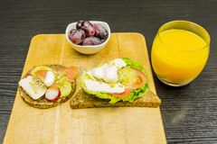 A healthy and nutritious breakfast. Board with sandwiches and grapes in a bowl. Drinking juice from freshly squeezed oranges Royalty Free Stock Images