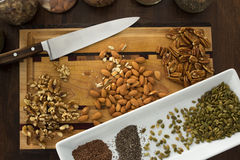 Healthy nuts and seeds on kitchen cutting board, with knife. Stock Photos