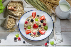 Healthy oat flakes with fresh fruits for breakfast. In the old rustic kitchen stock images