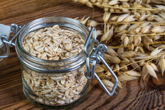 Healthy oat flakes in glass jar. Detail of rolled oats and natural oat on brown wooden background royalty free stock image